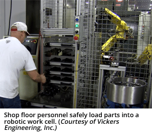Shop floor personnel safely load parts into a robotic work cell. (Courtesy of Vickers Engineering, Inc.)